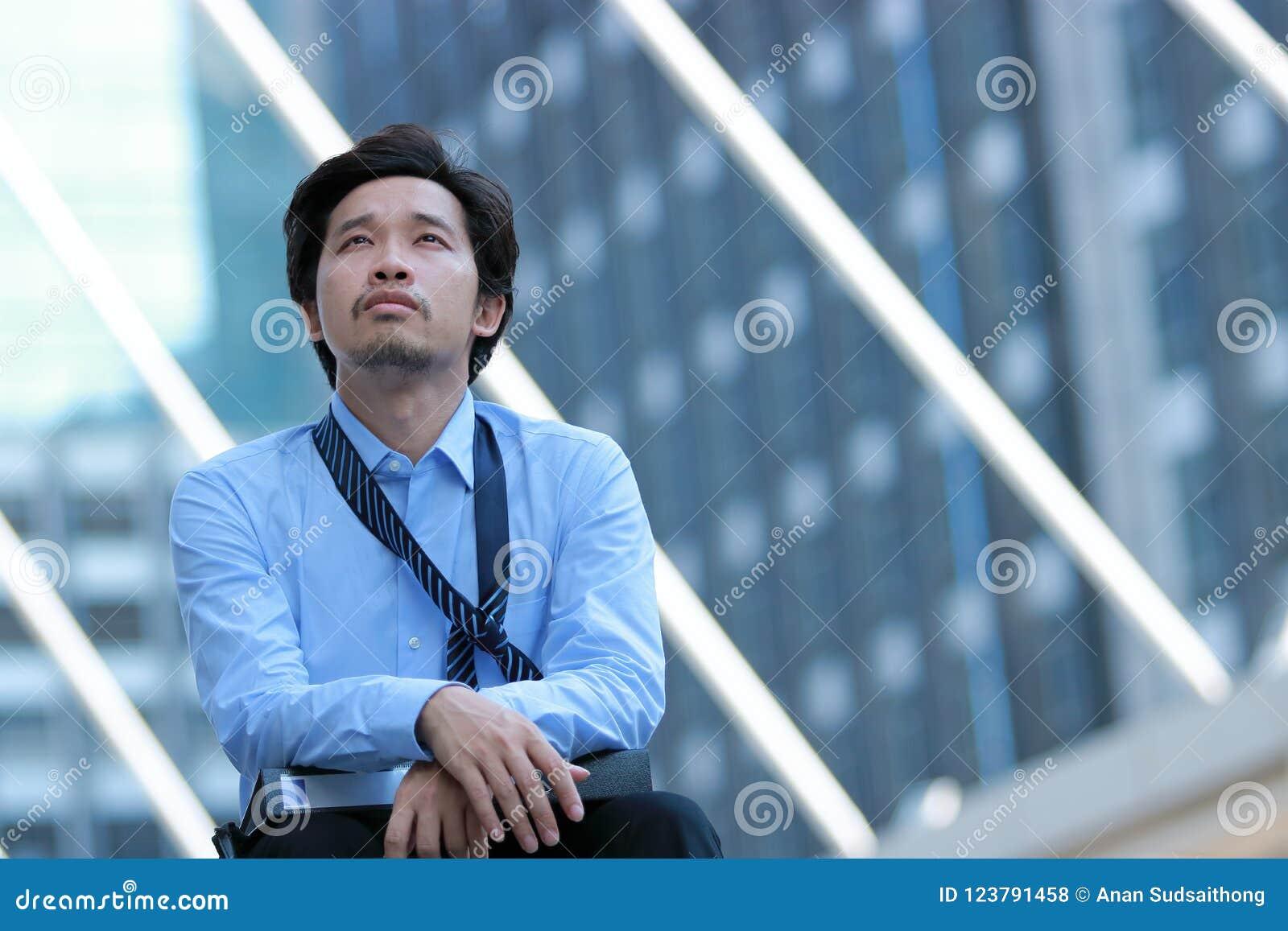 Frustrerad stressad ung asiatisk affärsmankänsla som evakueras, och huvudvärk mot jobb på stads- byggnad med kopieringsutrymmebac