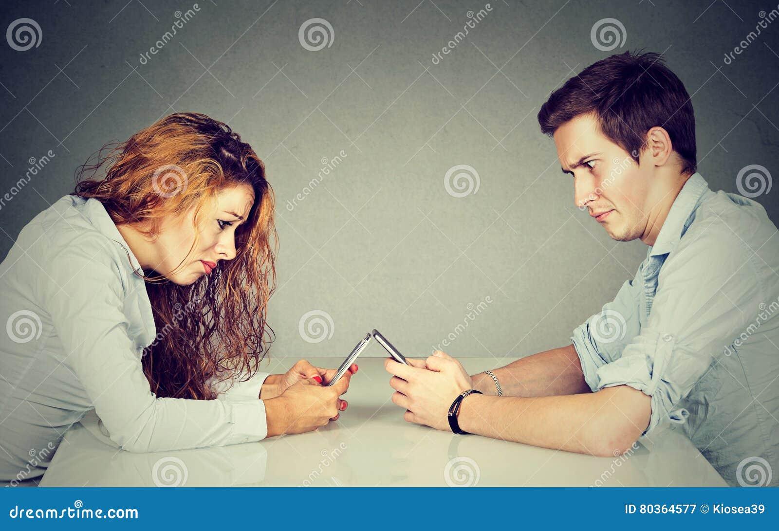 Frustrerat förargat ung kvinna- och mansammanträde på tabellen med smartphonen