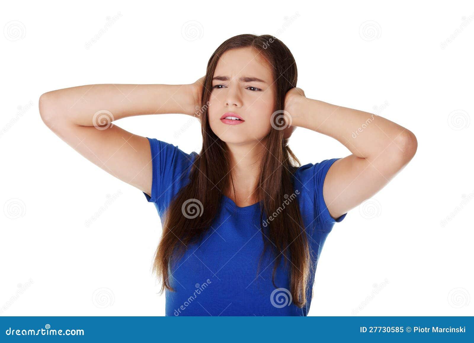 Frustrierte junge Frau, die ihre Ohren anhält