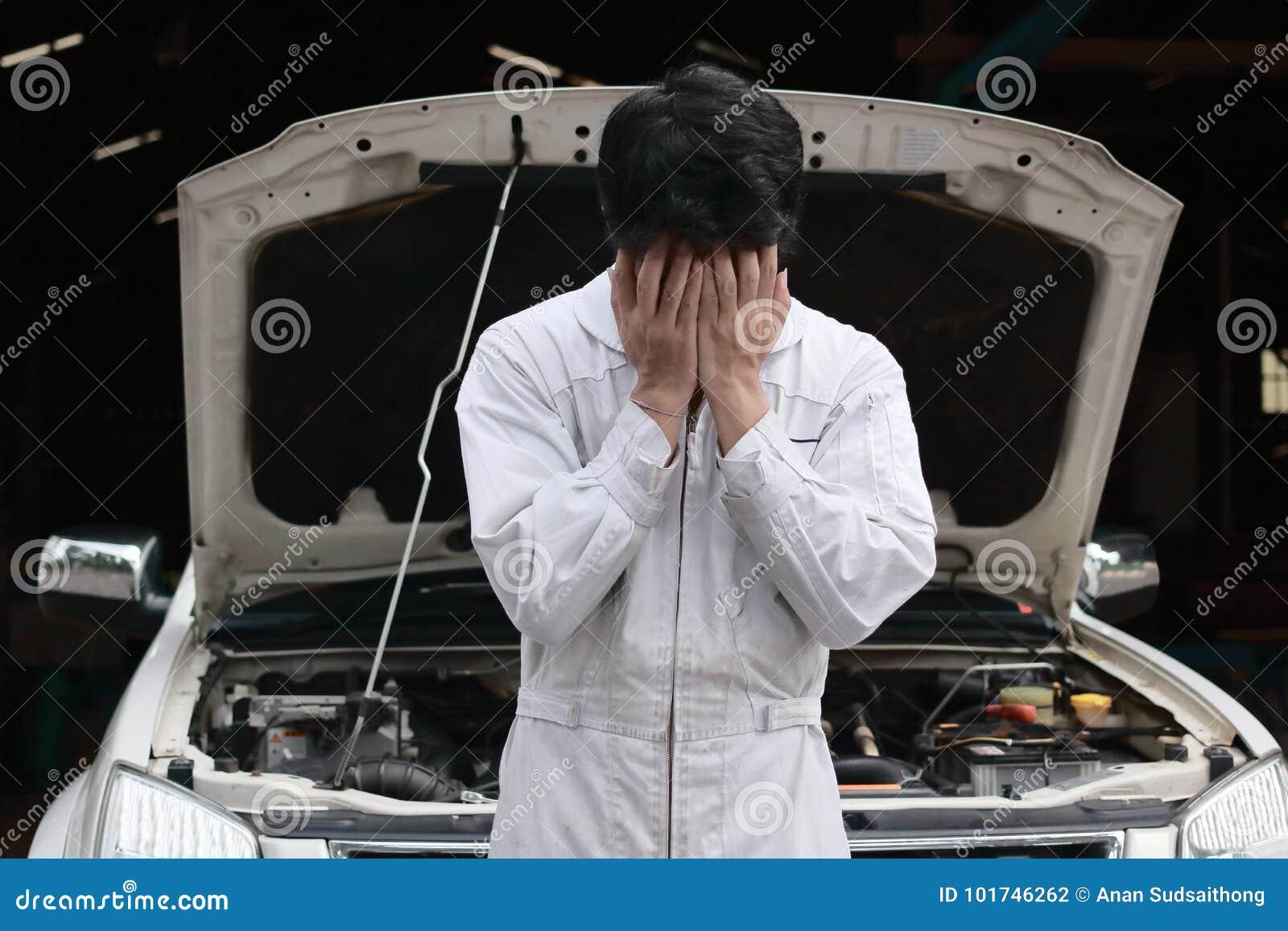 Frustrierter betonter junger Mechanikermann in der weißen Uniform, die sein Gesicht mit den Händen gegen Auto in der offenen Haub