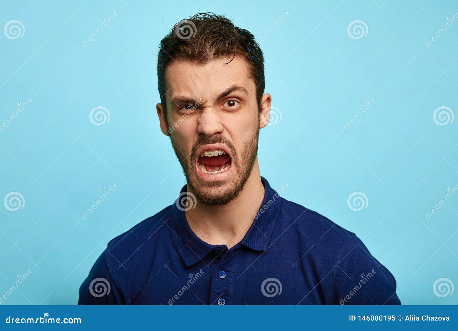 Frustrierter, erzürnter Mann mit mürrischer Grimasse auf seinem Gesicht,