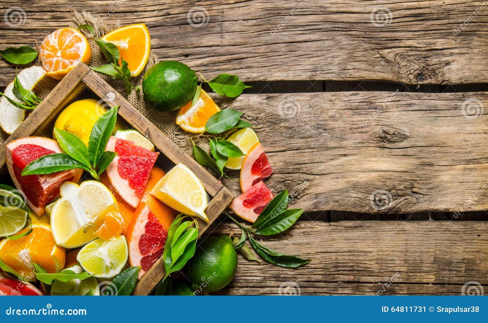 Fruta cítrica - pomelo, naranja, mandarina, limón, cal en una caja vieja