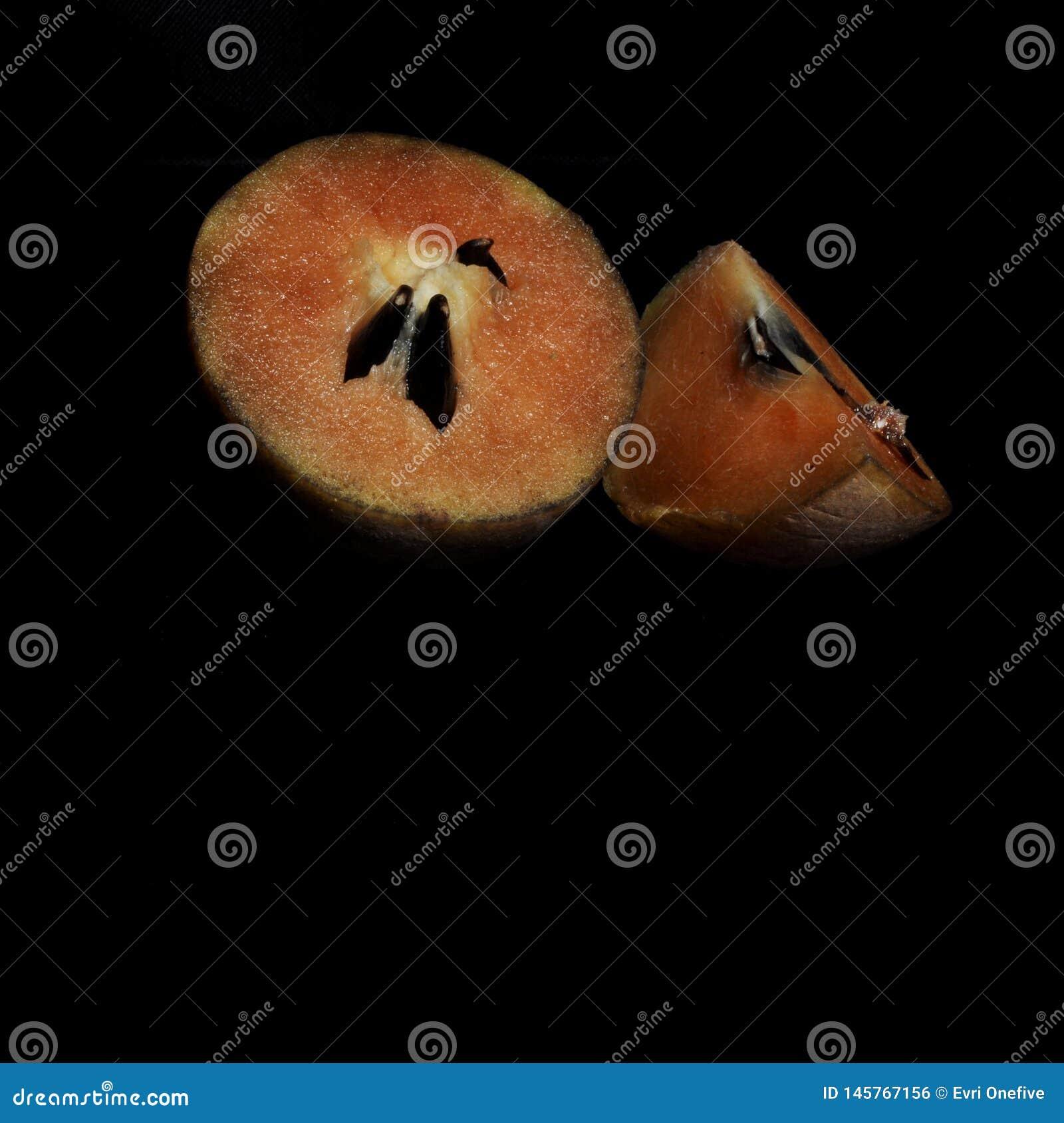 Fruta del zapote aislada en fondo negro