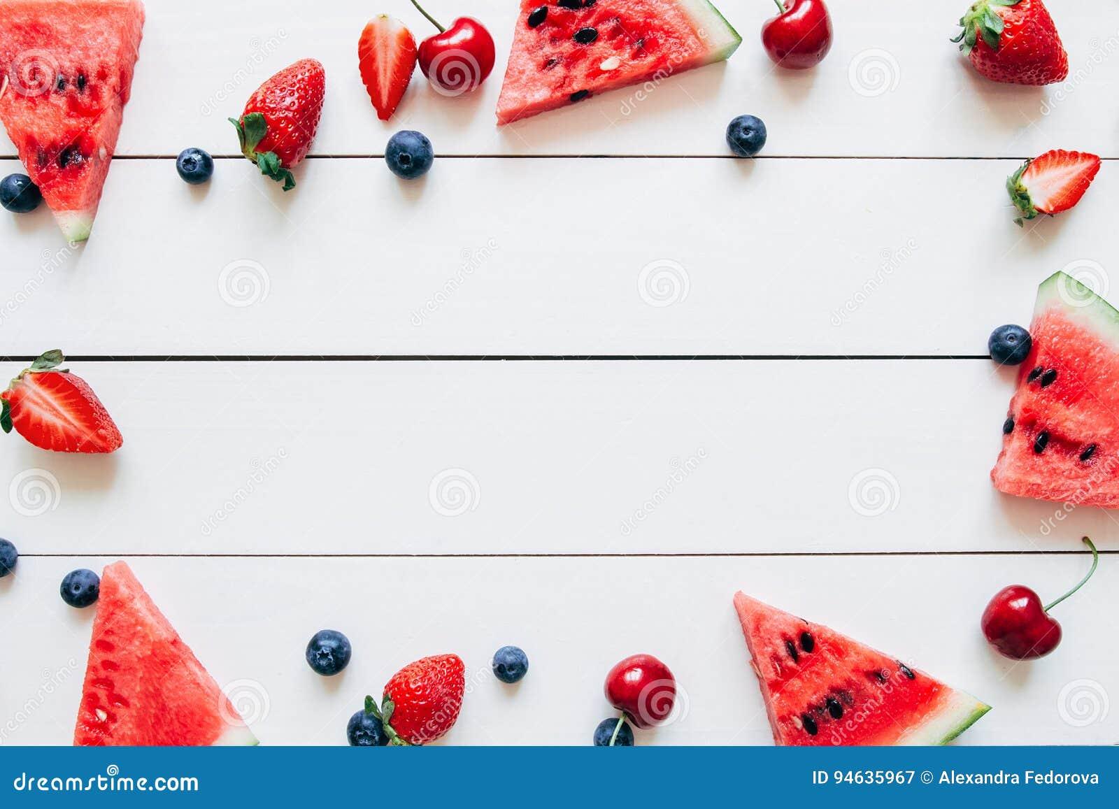 Frutas del verano Bayas y sandía jugosas frescas en la tabla de madera blanca, visión superior
