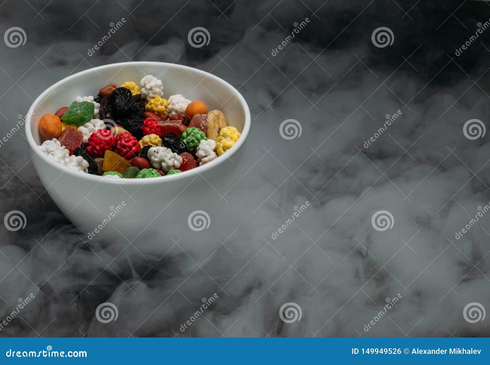 Frutas secadas en un cuenco en la tabla en el humo