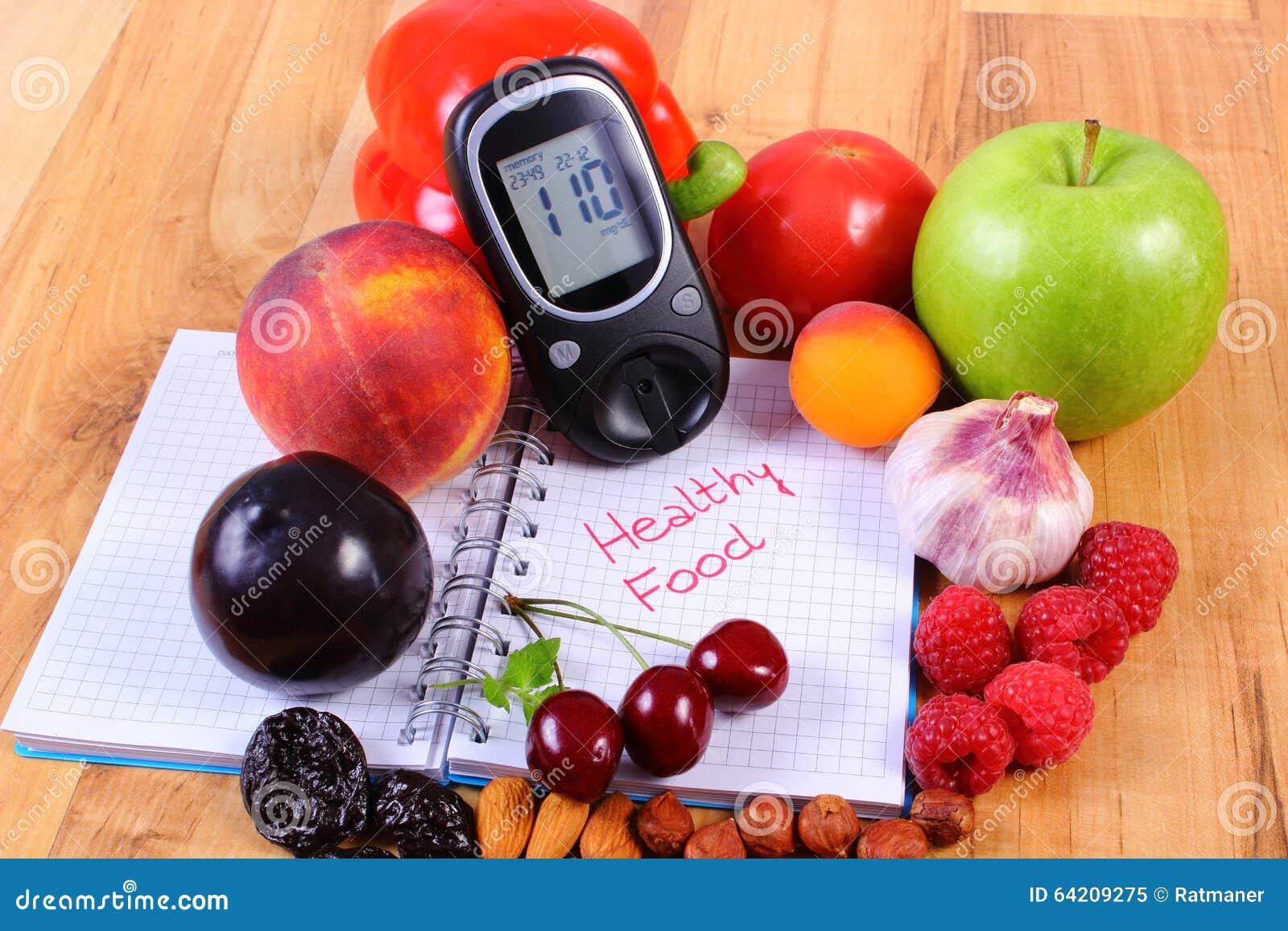 Frutas y verduras con el glucometer y el cuaderno para las notas, comida sana, diabetes