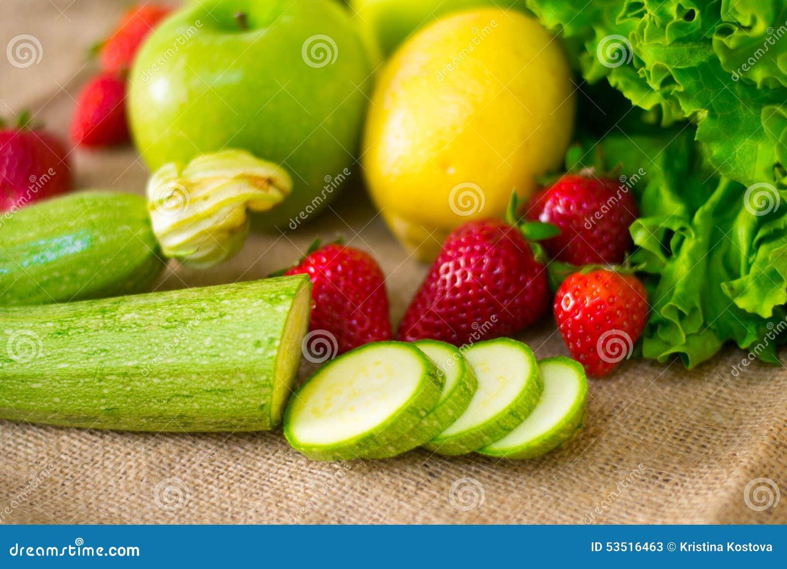 Fruto detalhado fresco - morangos, courgettes, limão, maçã e salada verde