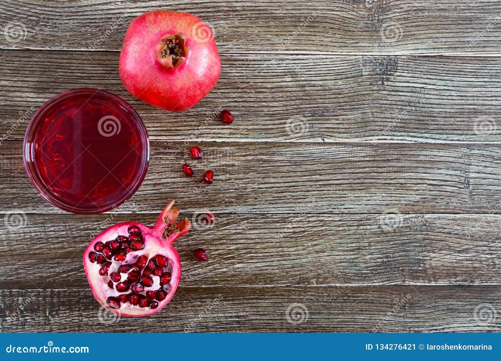 Fruto maduro da romã e um vidro do suco da romã na tabela de madeira Conceito saudável comer