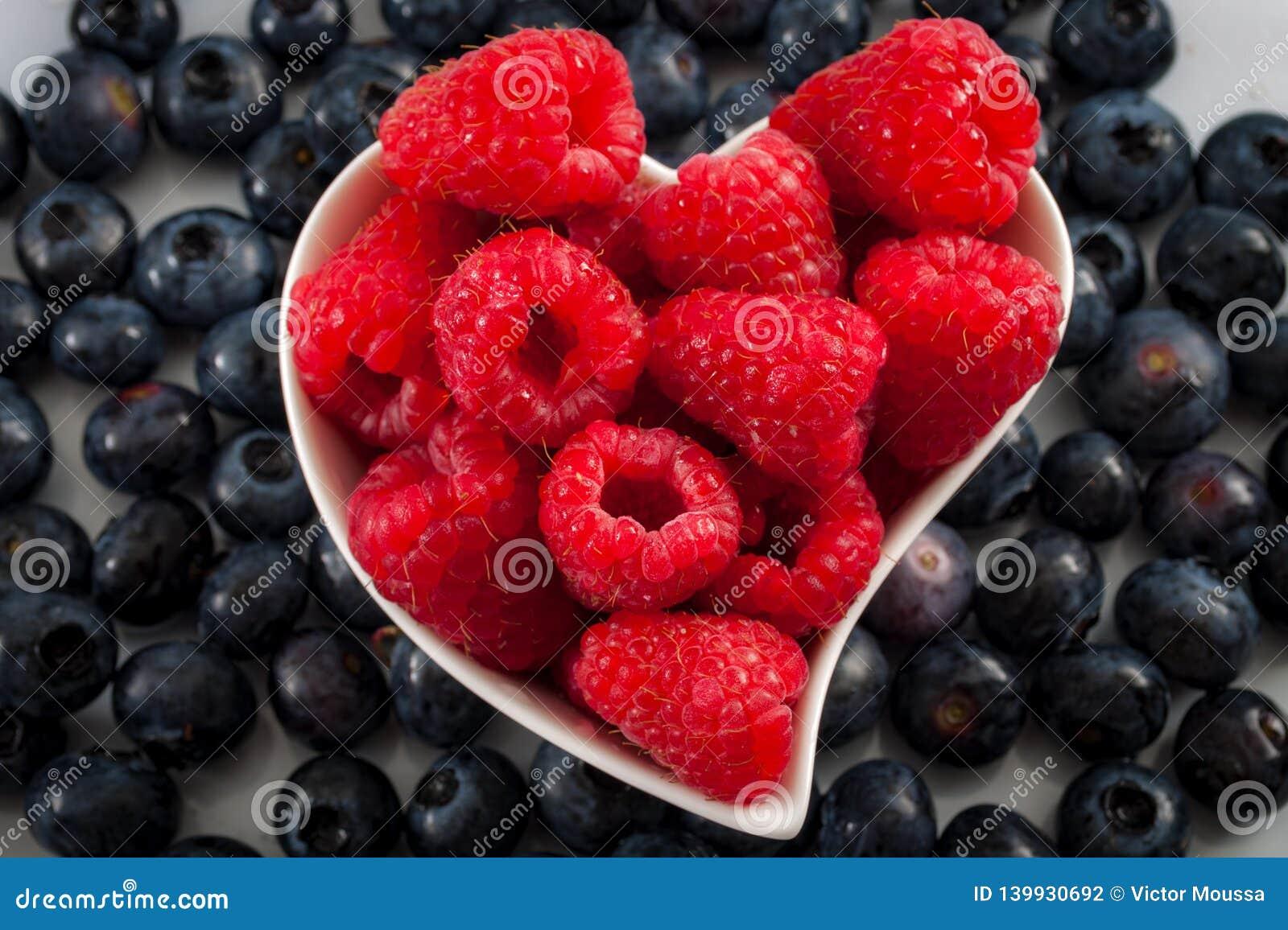 Frutos de baga frescos e conceito saudável comer com mirtilos e as framboesas misturados em uma bacia dada forma coração