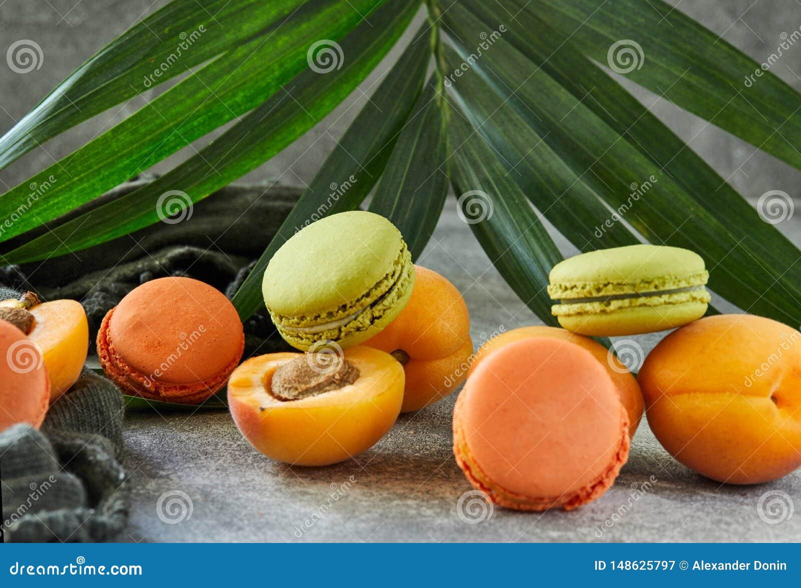 Frutos frescos e macaron no fundo de um ramo da palma