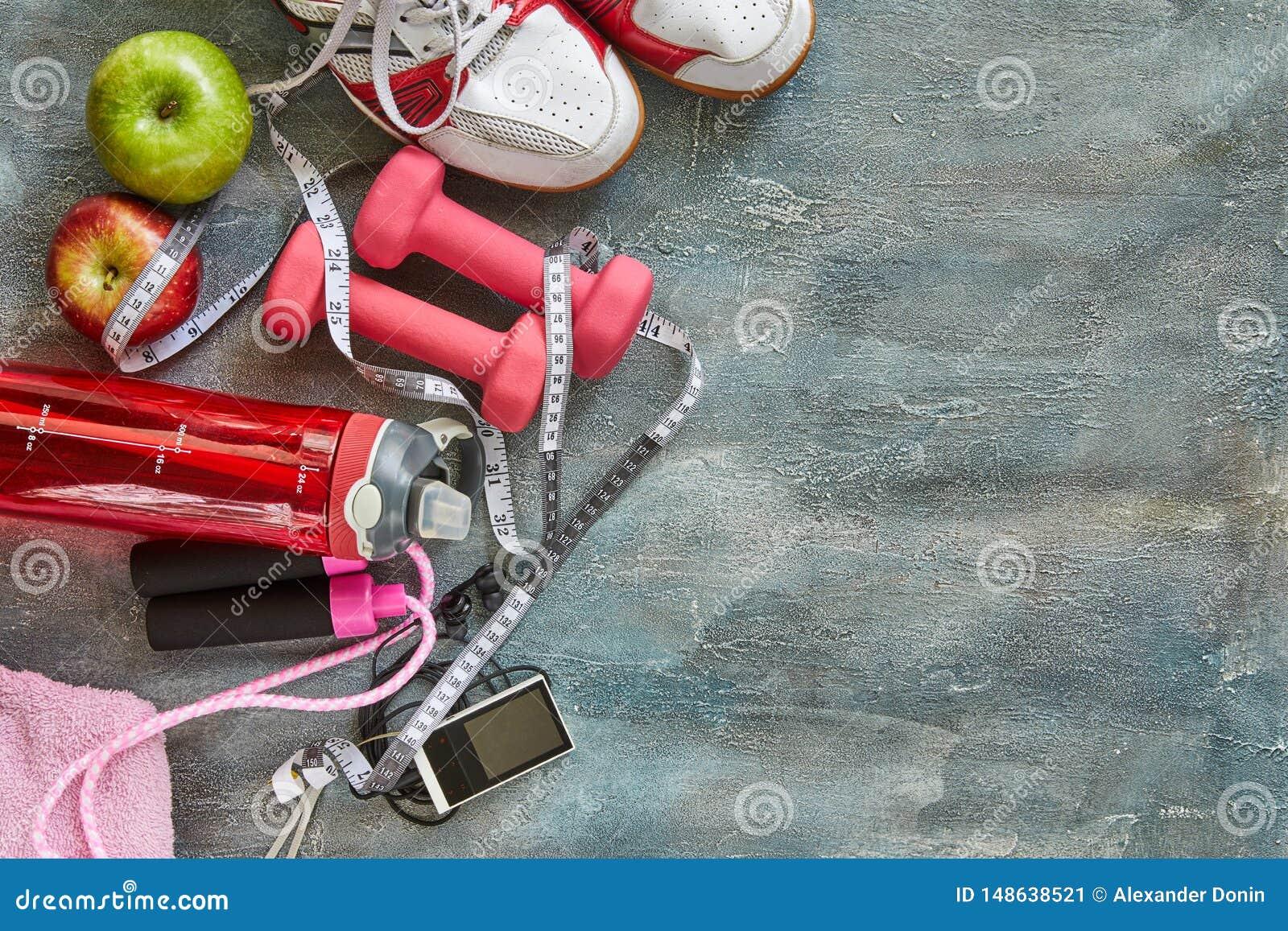 Frutos, pesos, uma garrafa da água, corda, sapatilhas e um medidor em um azul com fundo do divórcio