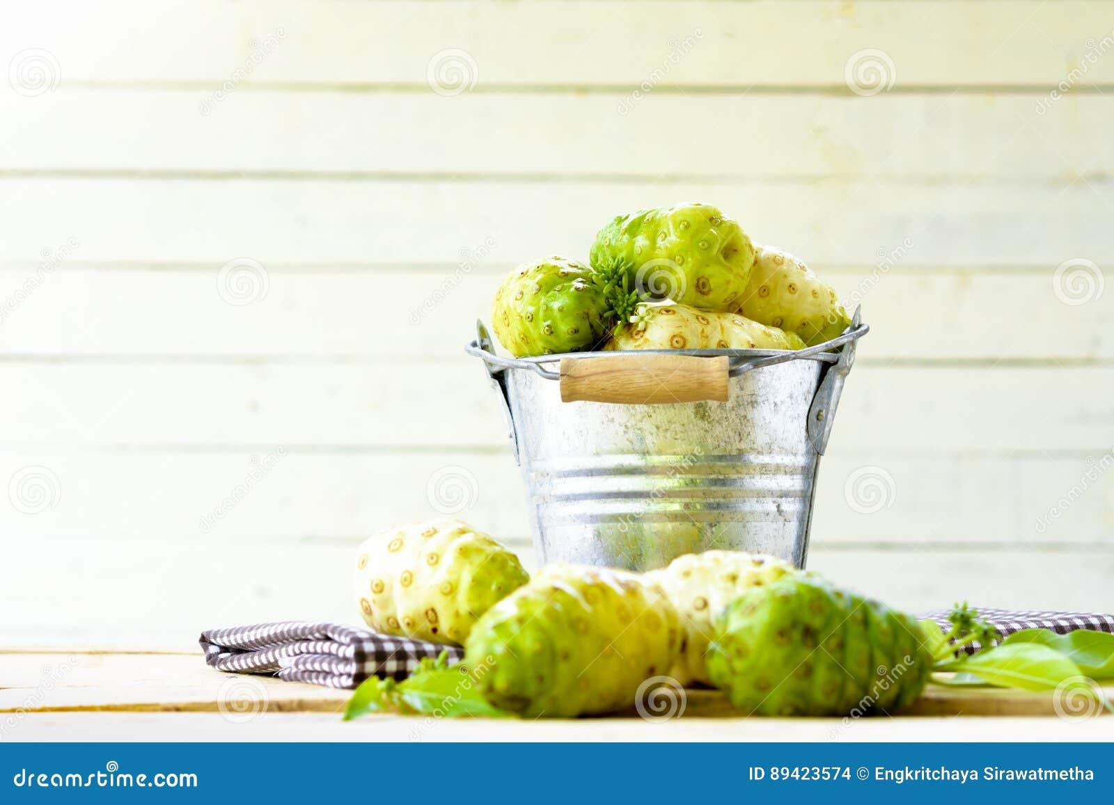 Frutta di Noni in secchio dello zinco e noni sulla tavola su fondo di legno bianco