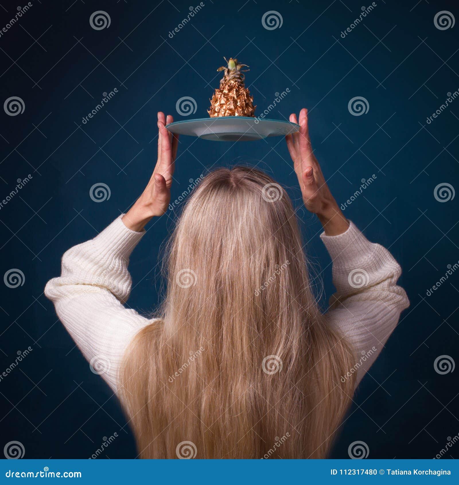 Frutta dorata dell ananas sopra la testa della donna