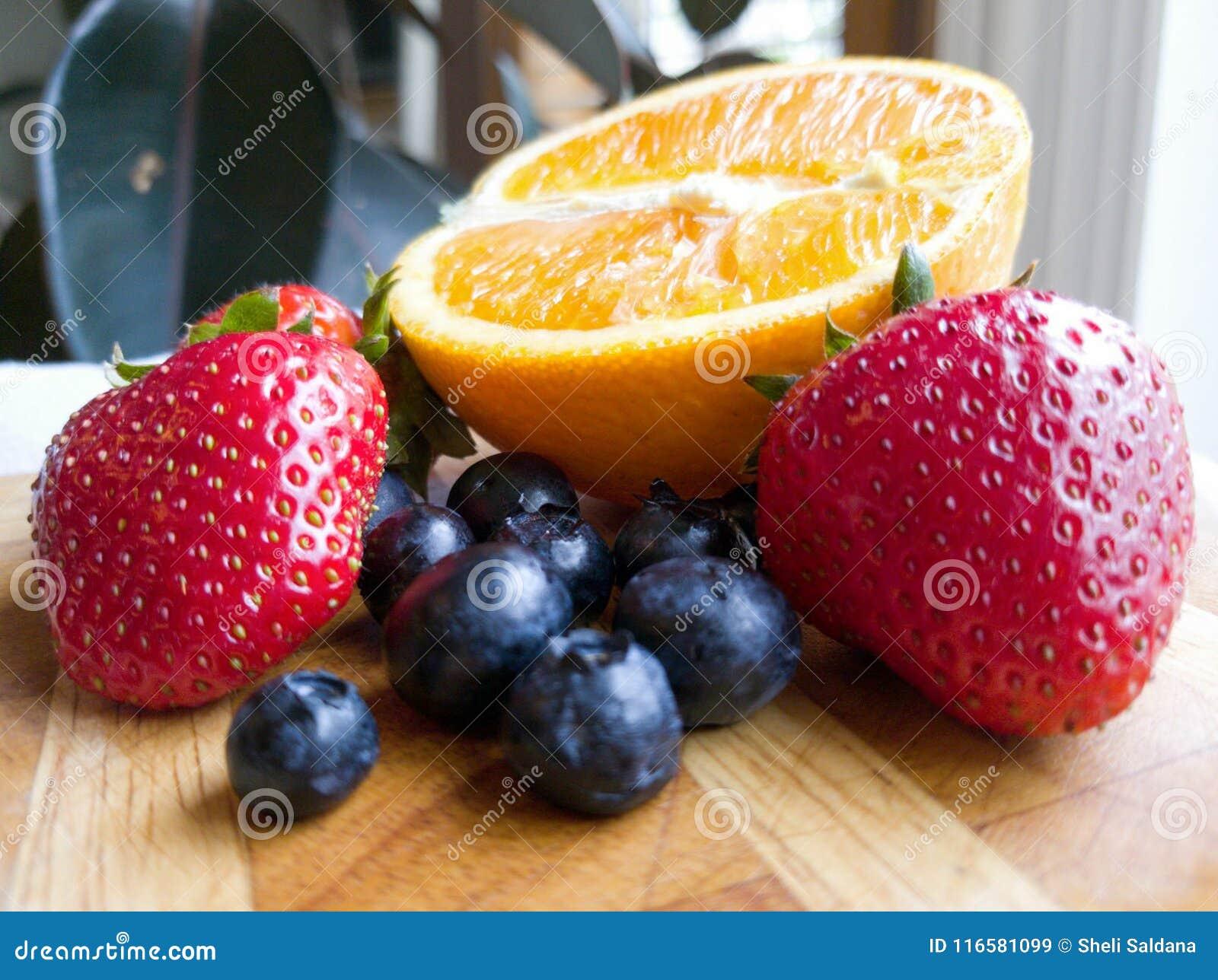 Frutti arancio del mirtillo della fragola sul tagliere di legno