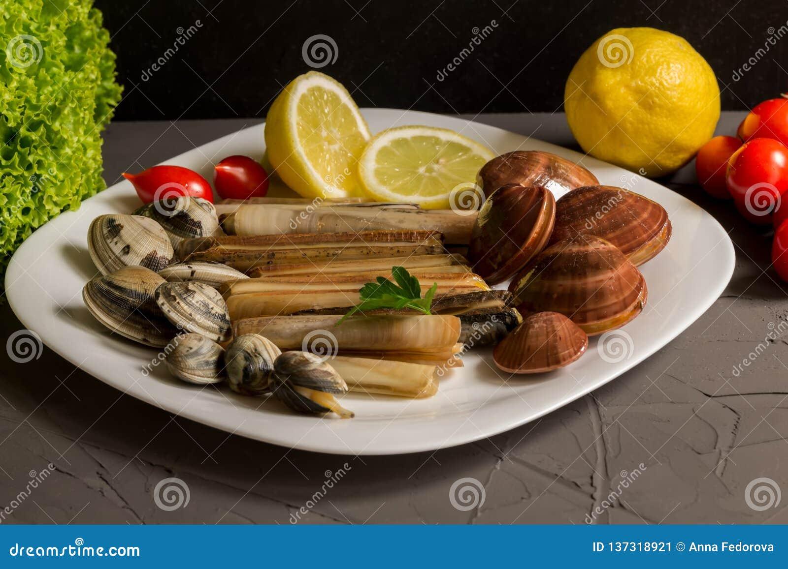 Frutti di mare freschi, vongole con il limone ed insalata su fondo grigio