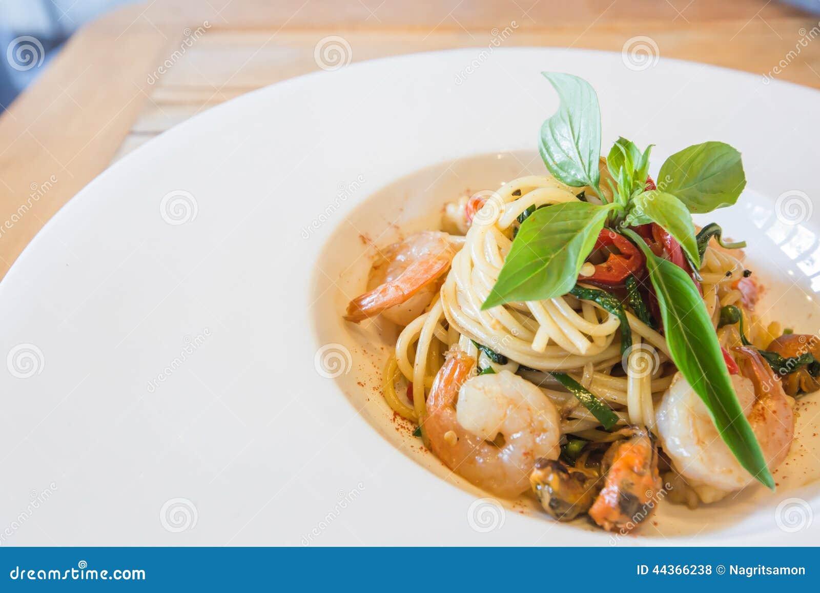 Frutti di mare piccanti degli spaghetti in piatto bianco