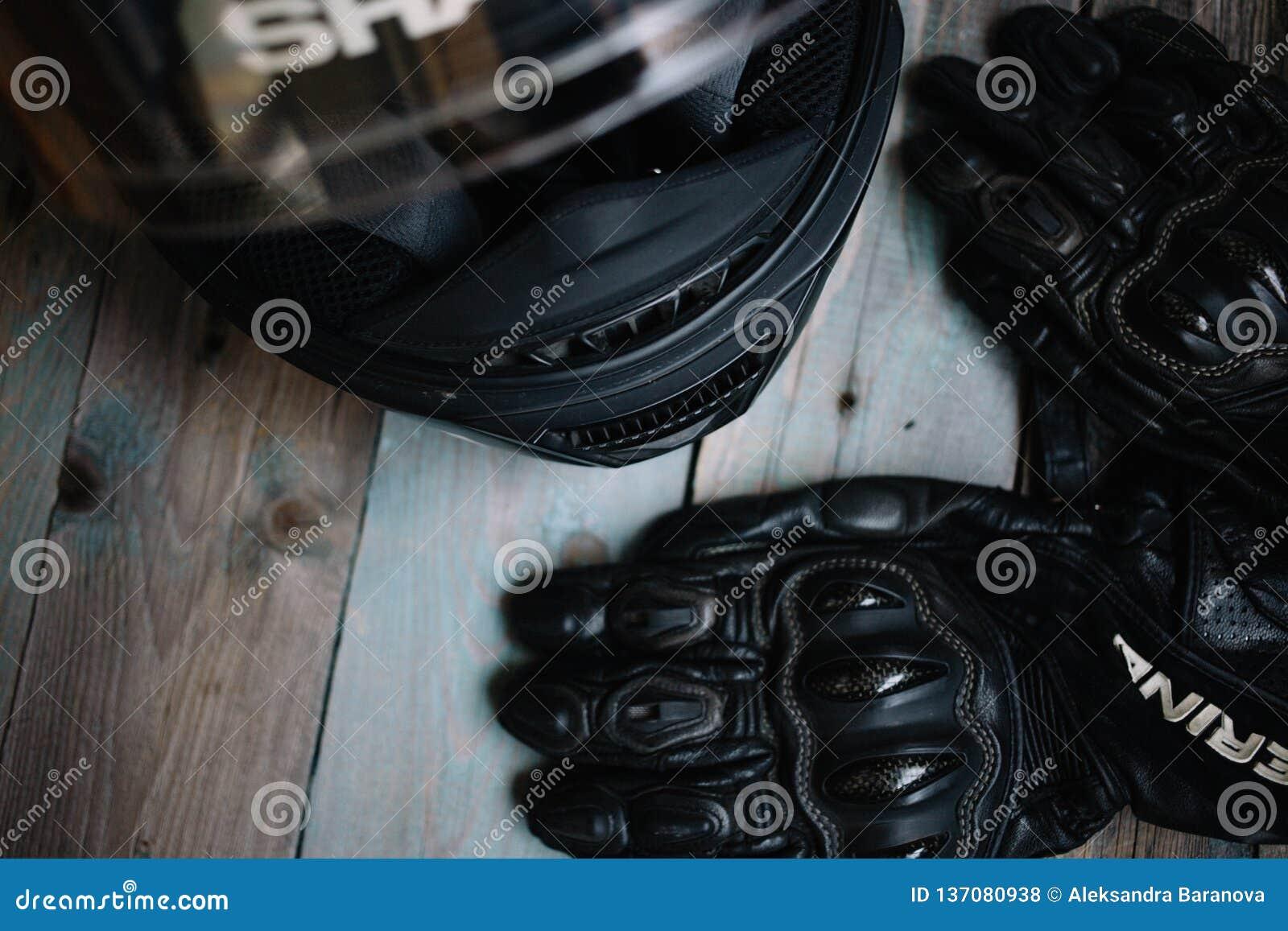 Fryazino, Rusland - 06 18 2018: motorrijdertoebehoren helm en handschoenen op houten lijst, hoogste mening