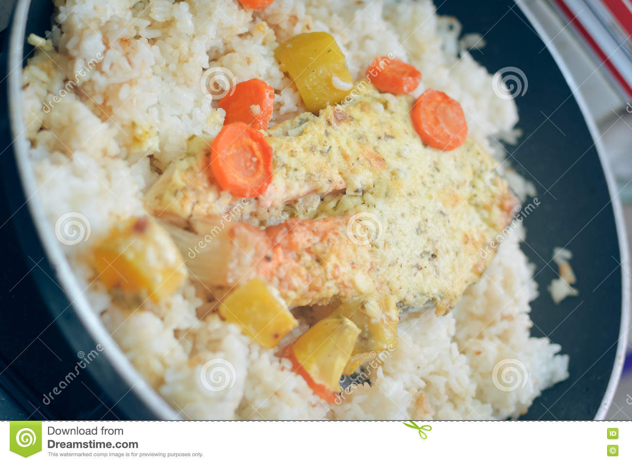 Frying pan with seafood salmon with rice and herbs. Top View.