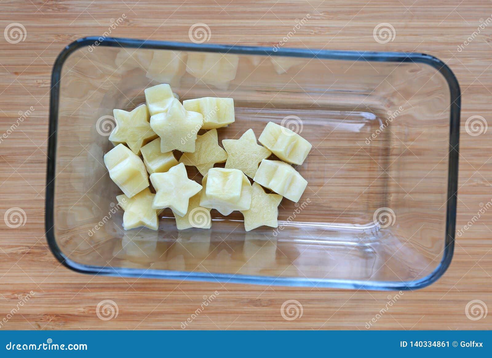 Fryst behandla som ett barn hemlagad mat, gul stjärna från grönsallatkuber i fyrkantig exponeringsglasbunke på träbräde