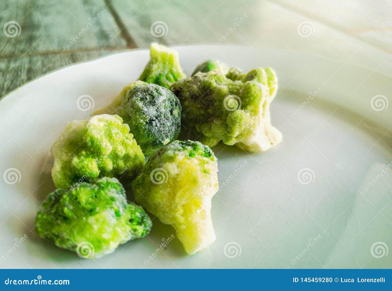 Fryste veggies glaserade broccoliisläggning utanför fryskylen