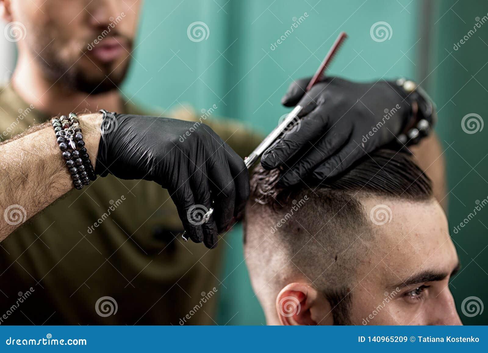 Fryzjer męski w czarnych rękawiczkach ciie z nożyce włosy elegancki mężczyzna przy zakładem fryzjerskim