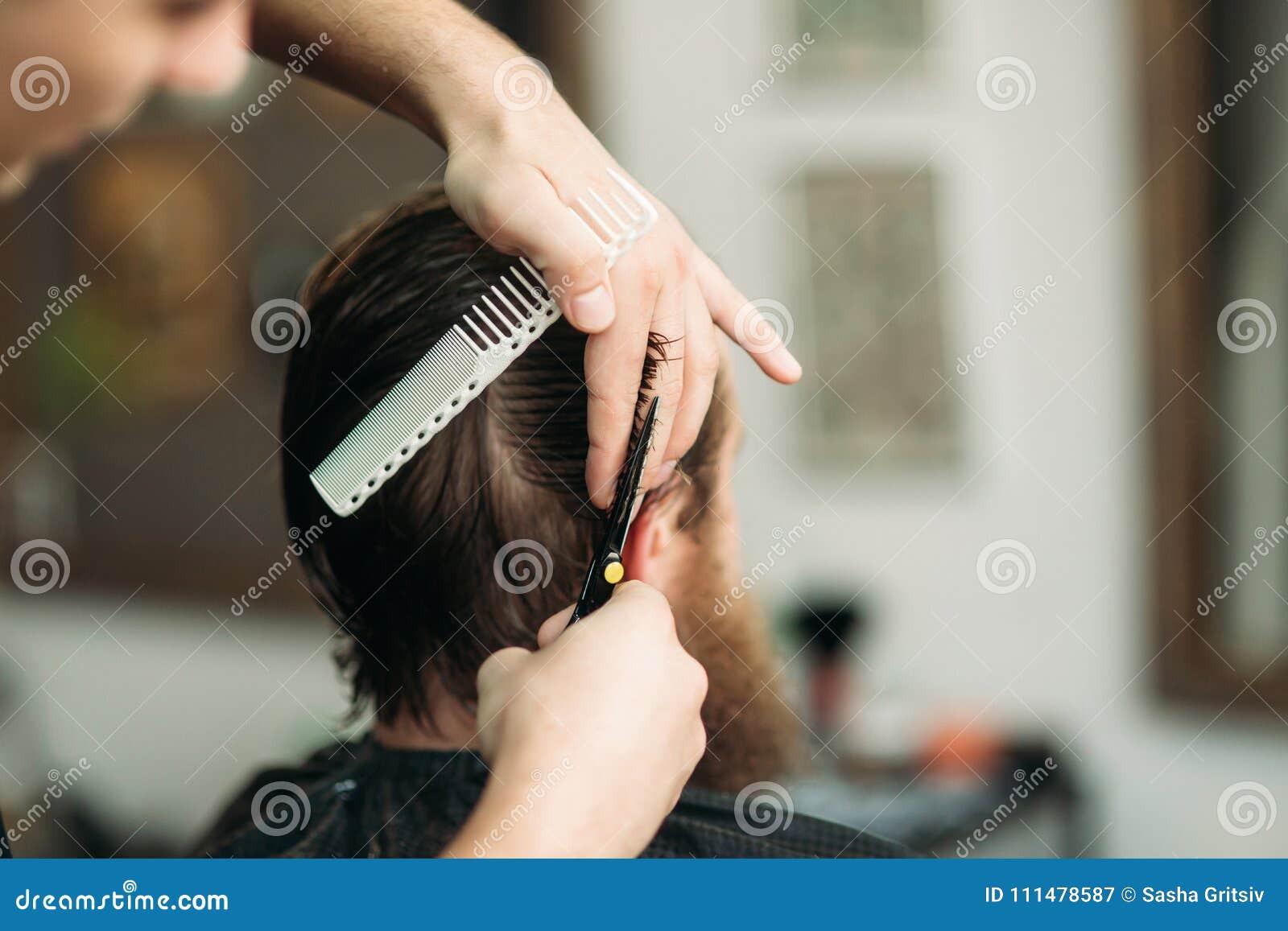 Fryzjer męski używa nożyce i gręplę w zakładzie fryzjerskim