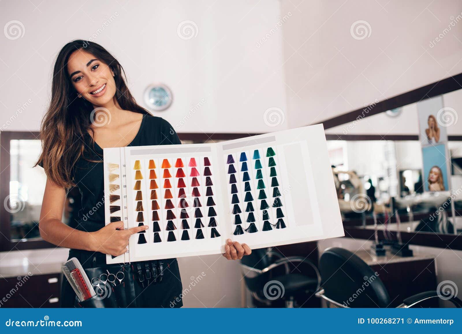 Fryzjer pokazuje włosianą koloru cienia kartę przy salonem