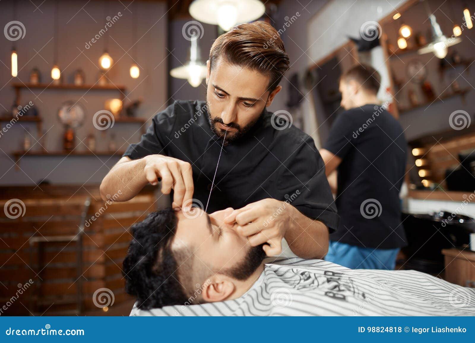 Fryzjer pracuje przy zakładem fryzjerskim, koryguje chleb z białą nicią