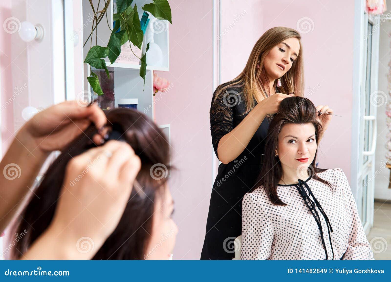 Fryzjer przy pracą - fryzjer robi włosy piękna młoda brunetka klient w piękno salonie