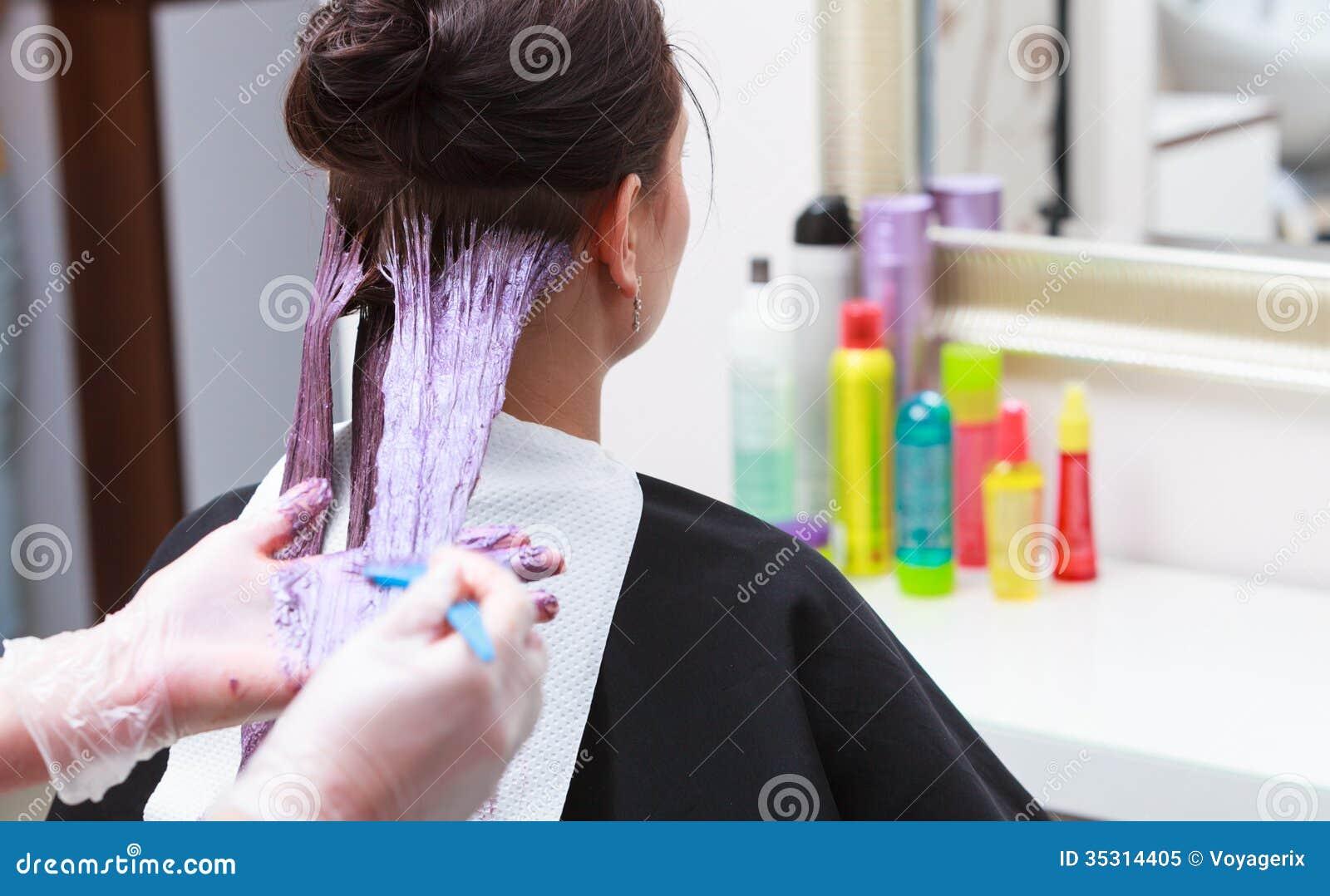 Fryzjer stosuje koloru żeńskiego klienta przy salonem, robi włosianemu barwidłu