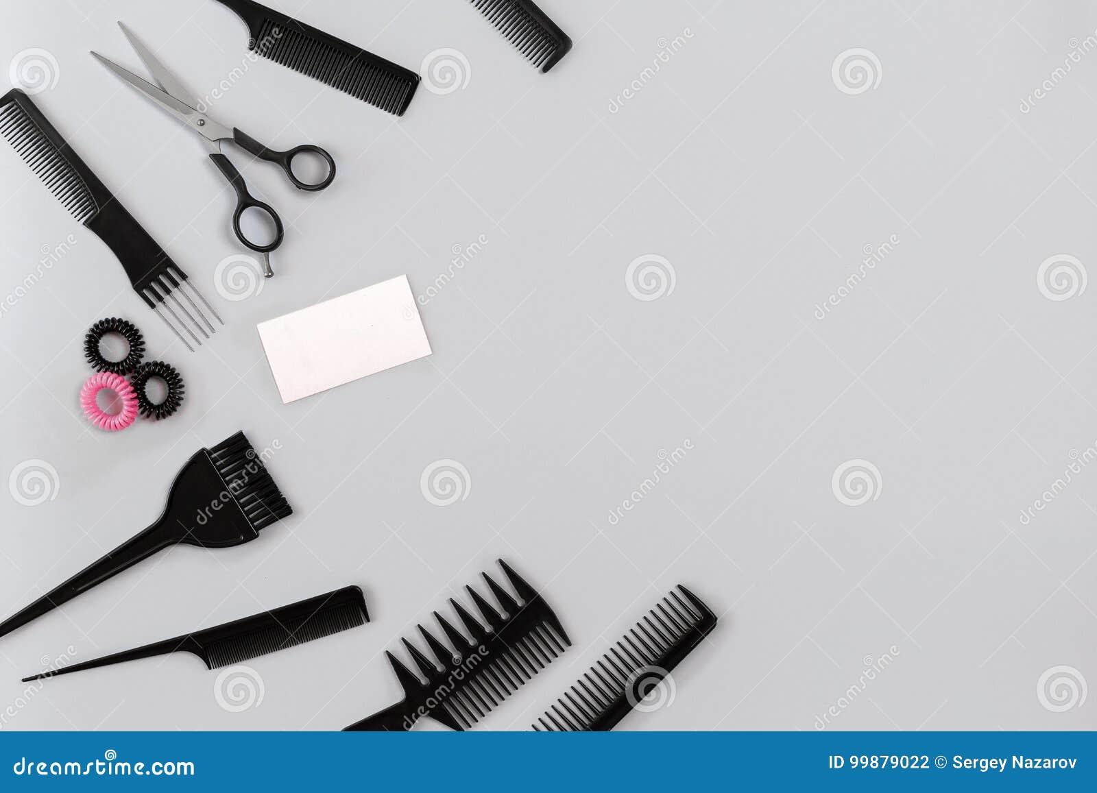 Fryzjer ustawiający z różnorodnymi akcesoriami na szarym tle