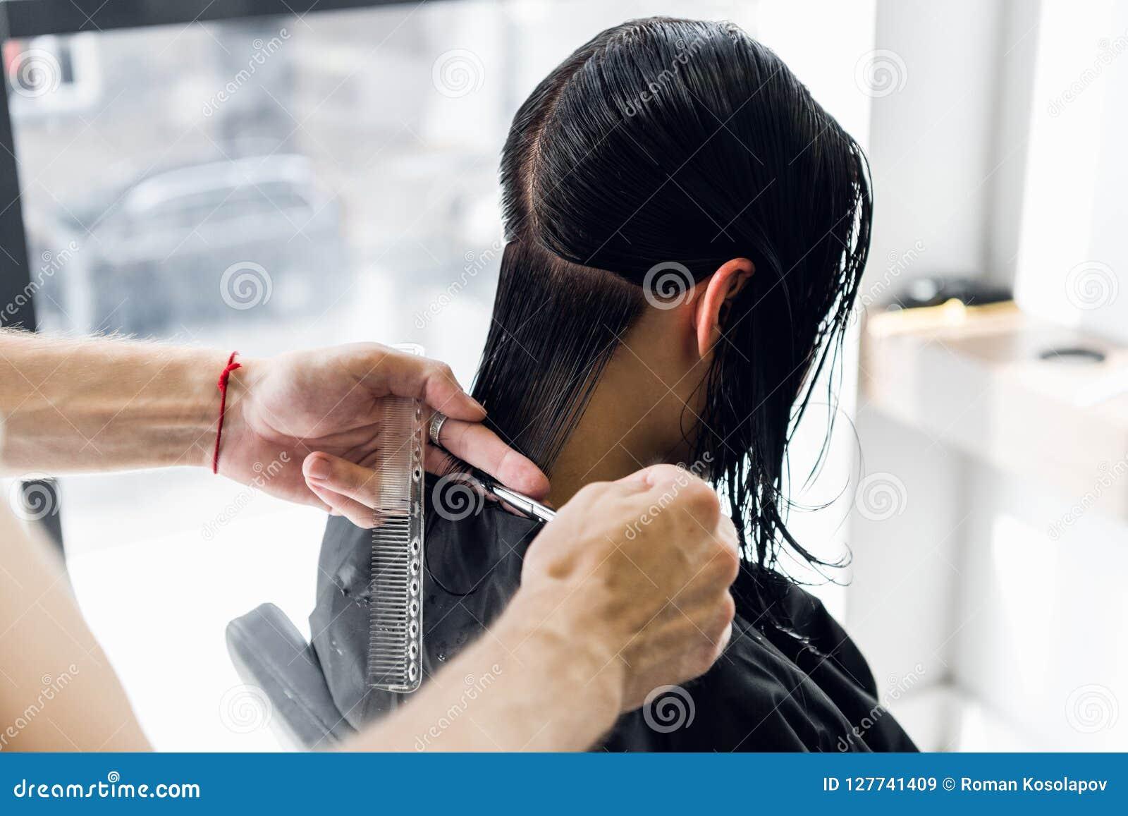 Fryzjera klienta ` s tnący włosy w salonie z nożyce zbliżeniem Używać gręplę