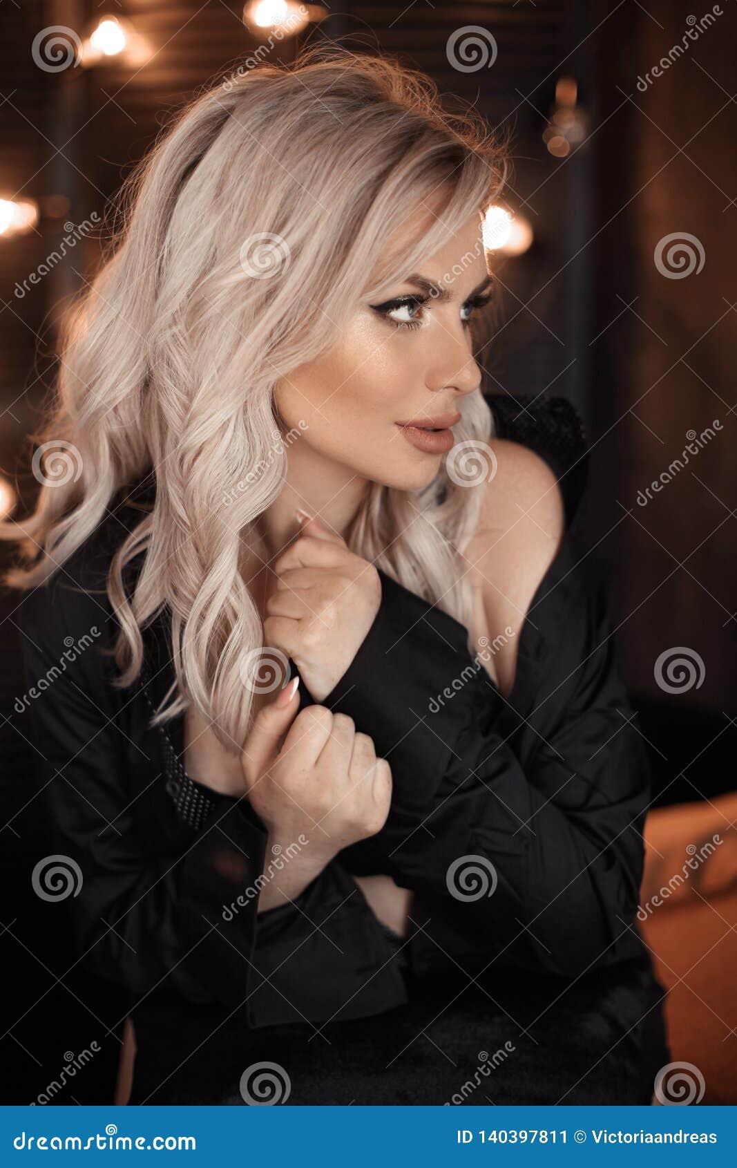 Fryzury Piękny blondynki kobiety portret pozuje w czarnej koszula Modny blond dziewczyna model nad bokeh zaświeca ciemnego tło