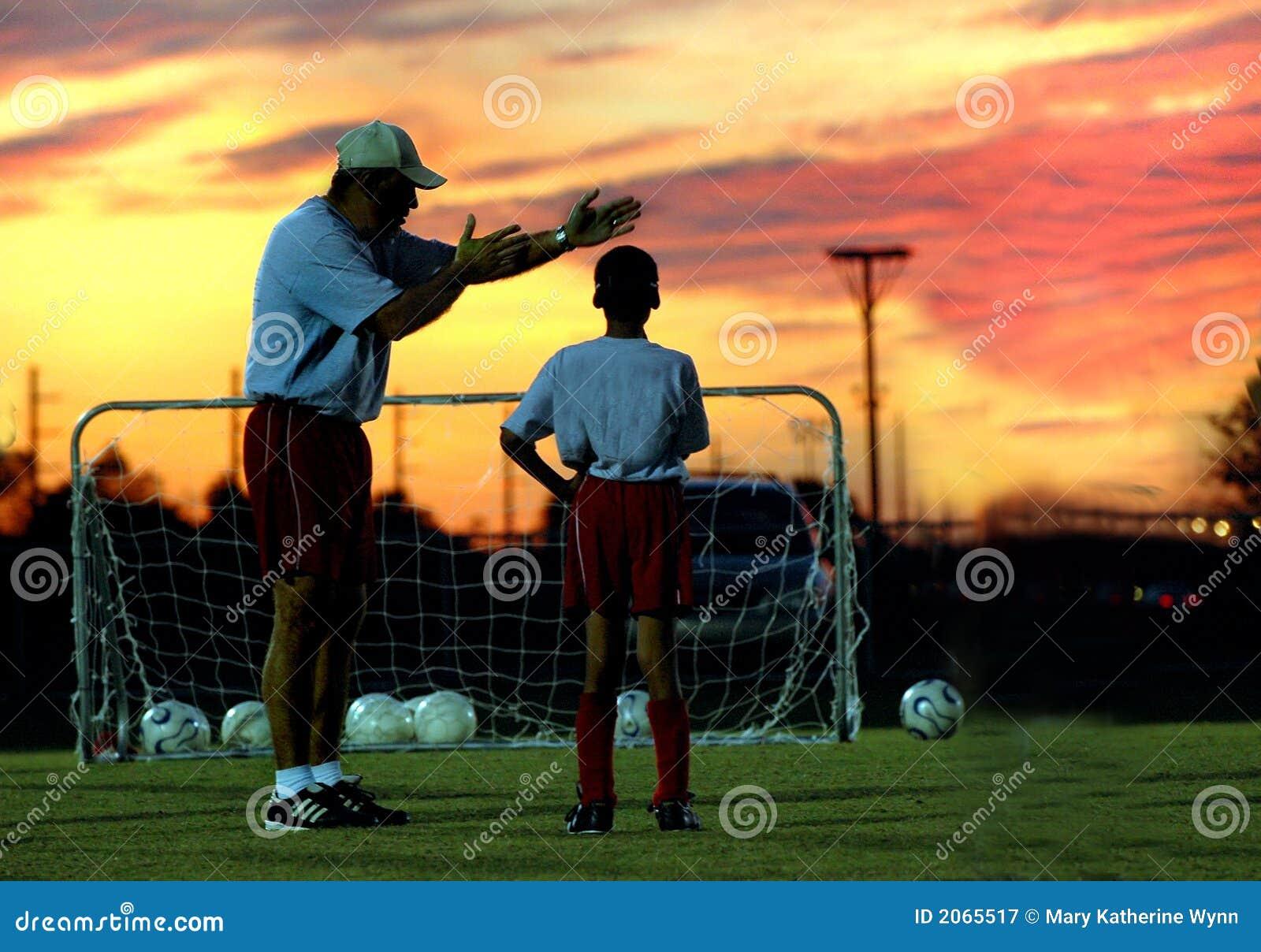 Fußball, der am Sonnenuntergang trainiert