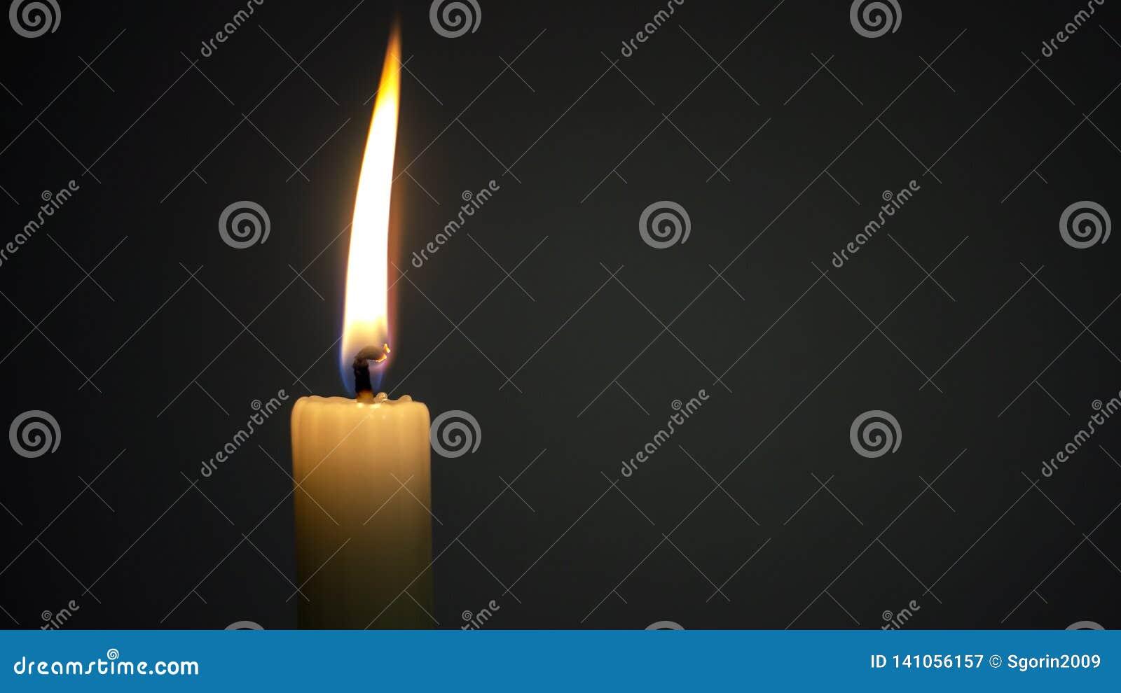 Fuego ardiendo de la vela en oscuridad