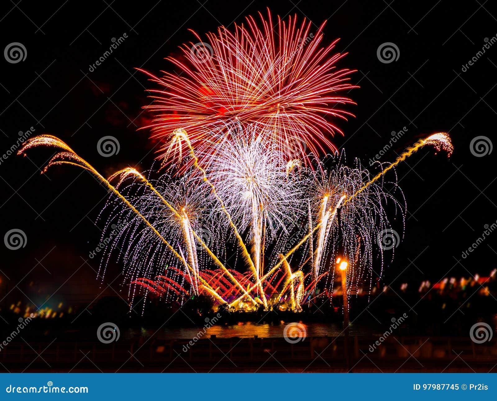 Fuegos artificiales coloridos con explosiones múltiples contra el cielo oscuro