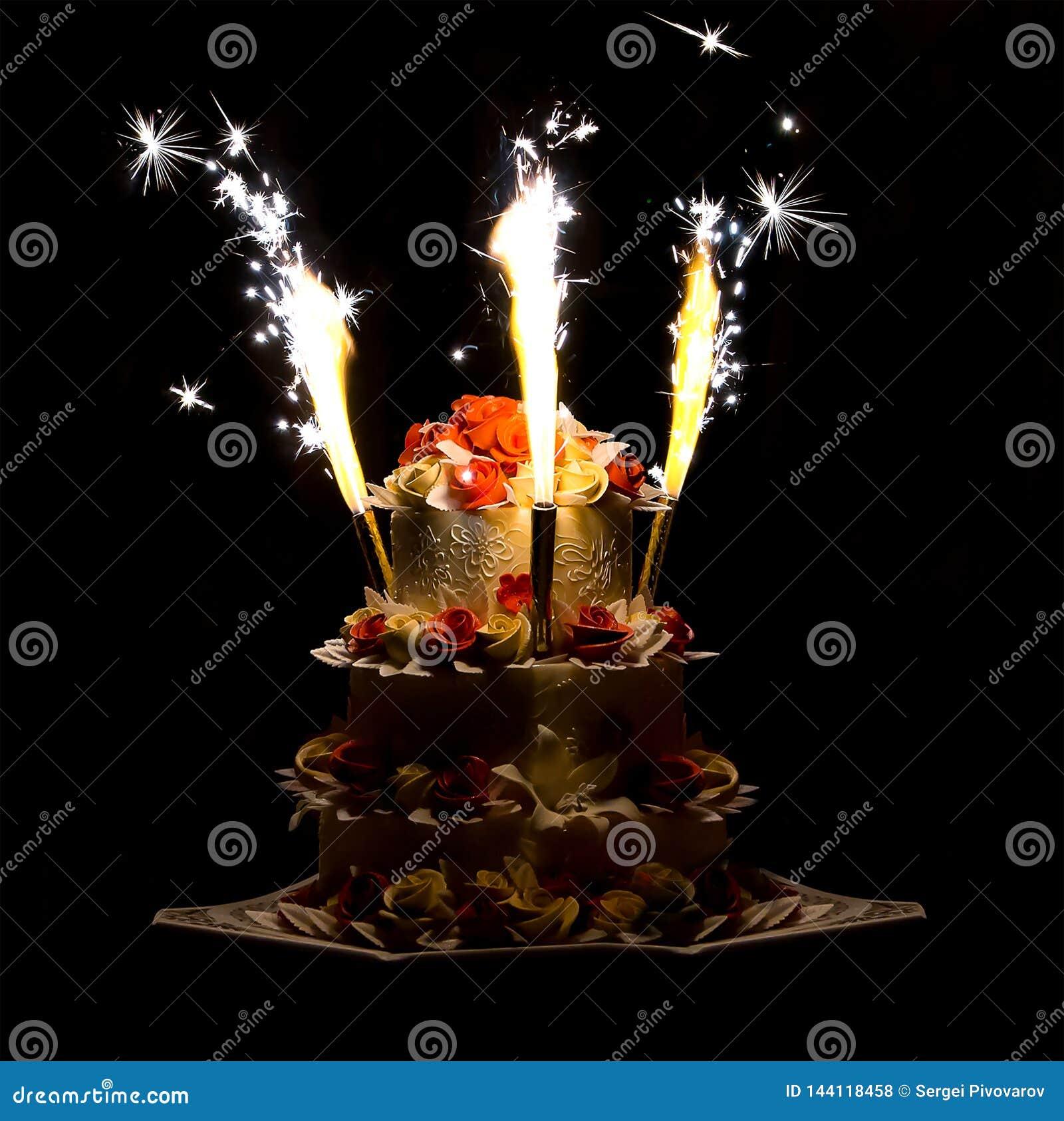 Fuegos artificiales coloridos de la torta brillante festiva en un fondo oscuro que pone en contraste el fondo que se casa colorid