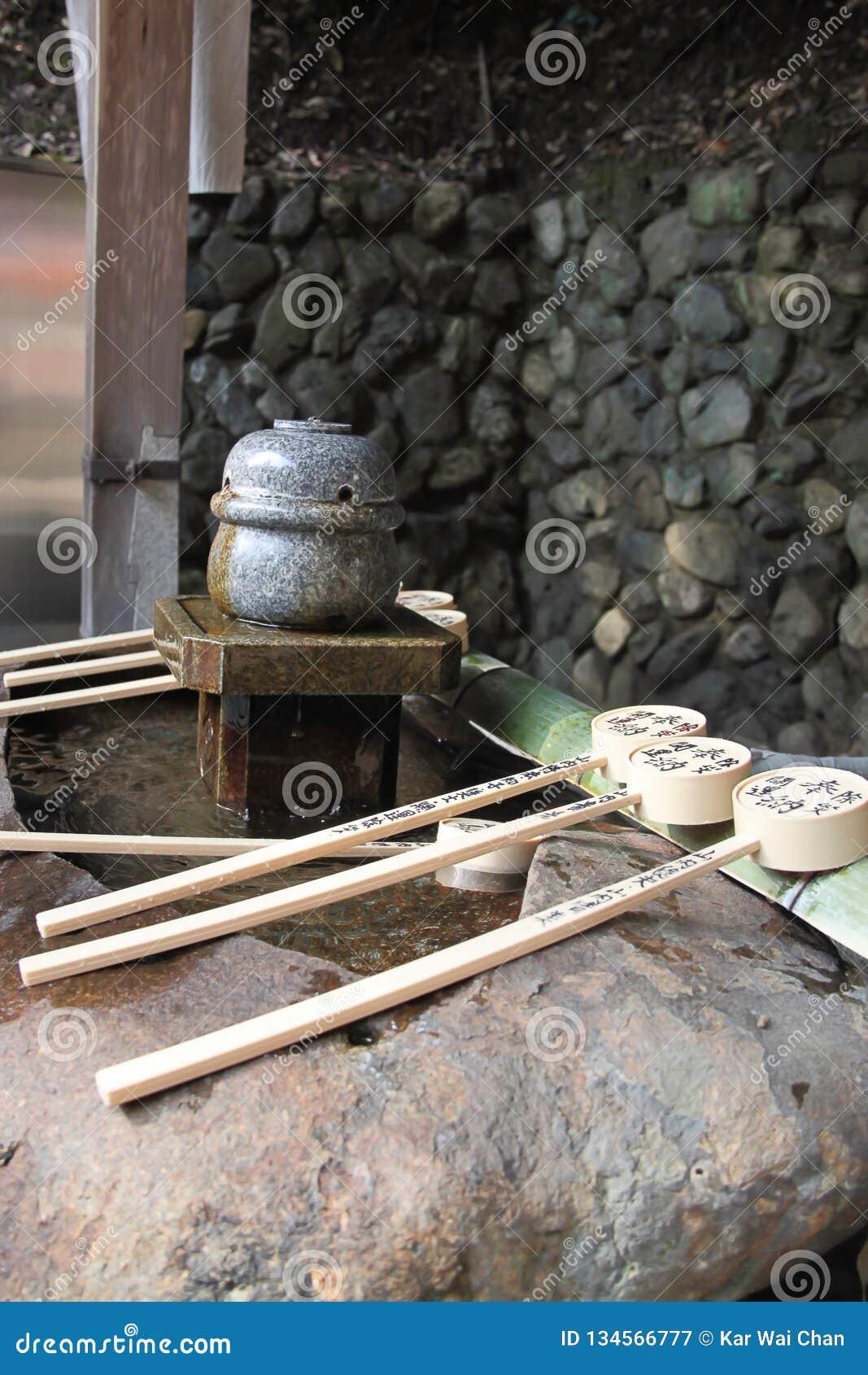 Fuente de la purificación con la cucharón en una capilla japonesa