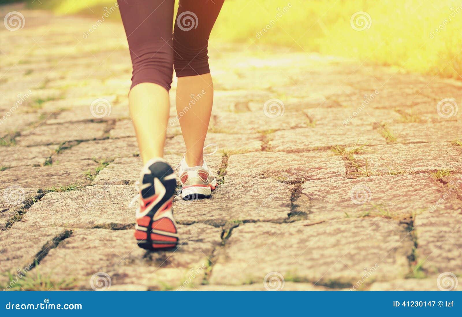 Fuga rural de passeio dos pés do caminhante da jovem mulher