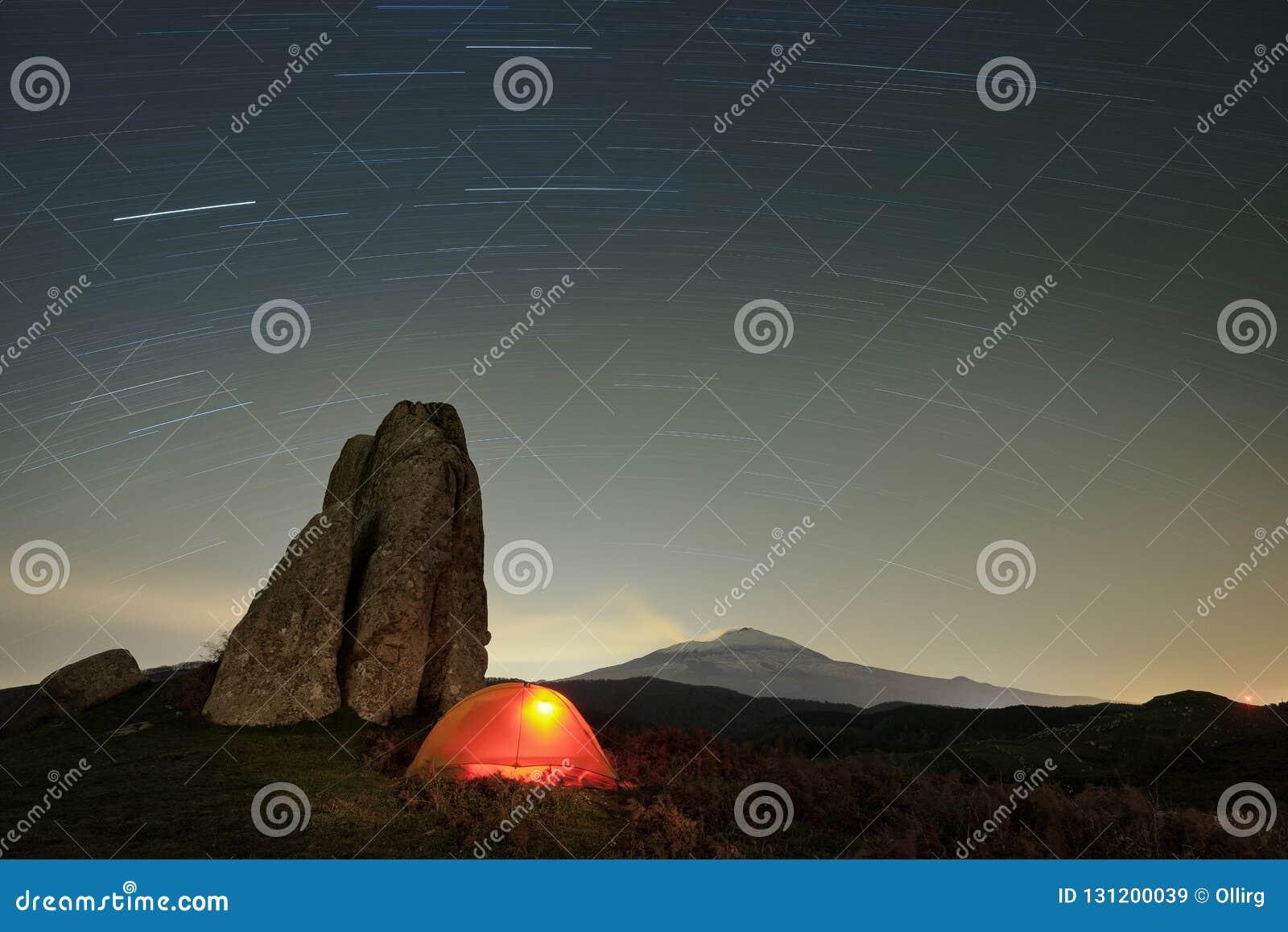 Fugas das estrelas em iluminar a barraca em montanhas de Argimusco, Sicília
