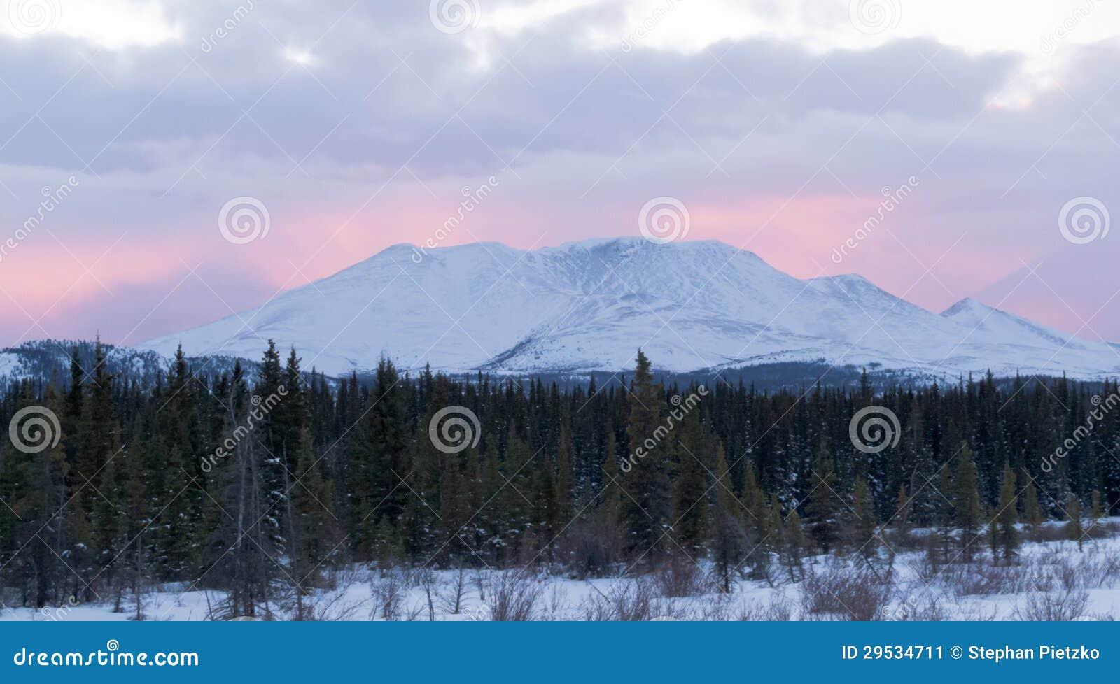 Fulgor do por do sol atrás winterly de pouco pico YT Canadá