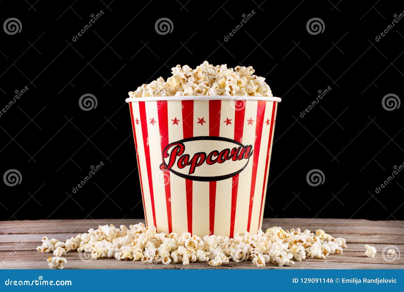 Full ask med popcorn och som spiller på det retro träskrivbordet