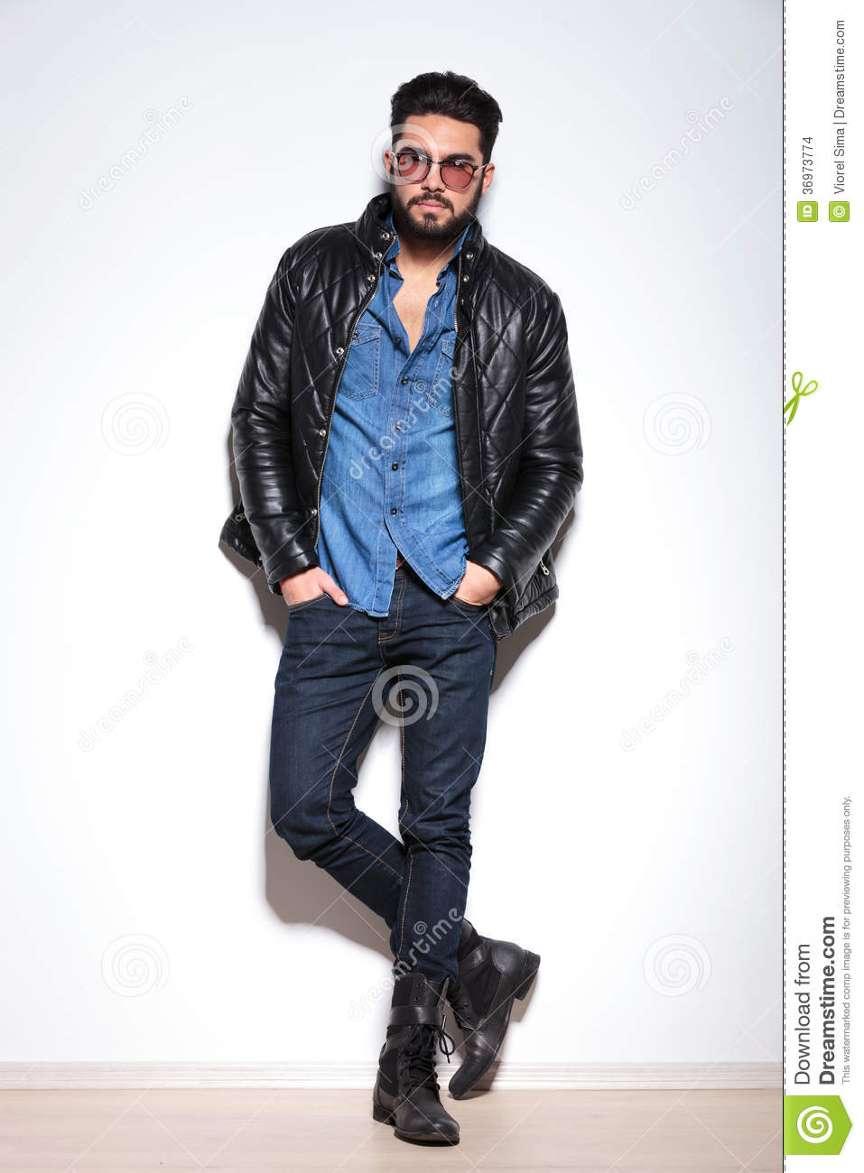 Casual Man In Leather Jacket Jeans And Boots Against Studio Wall
