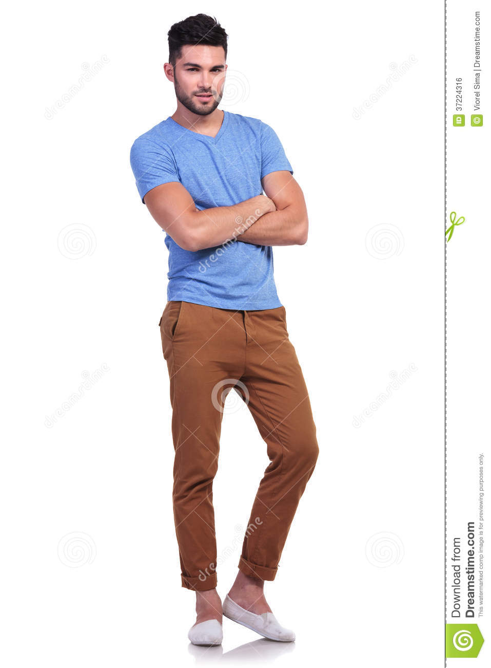 full body picture of a young man with hands crossed stock photo