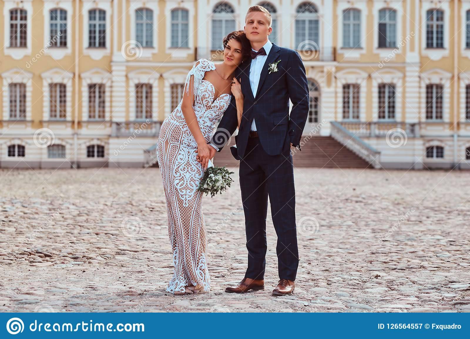Portrait of happy newlyweds embracing against the backdrop of the facade of the beautiful old palace.