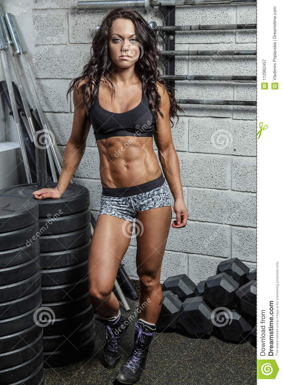 Full body portrait of sporty female with barbell.