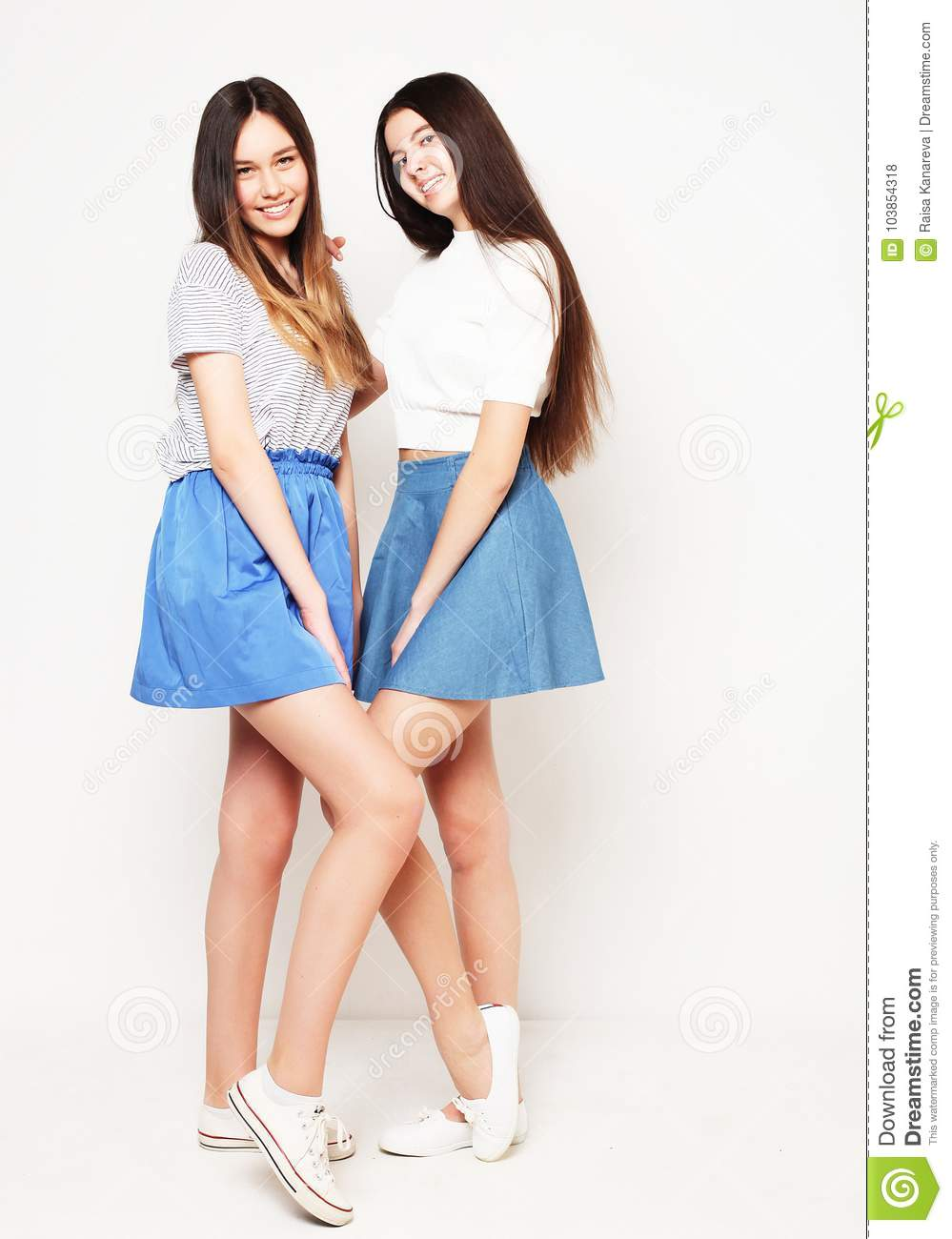 Full body portrait of two happy girls over white background