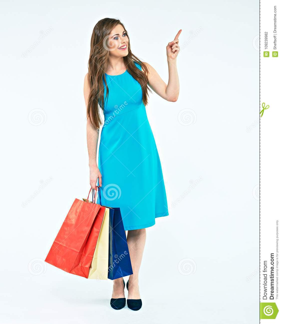 Full body portrait of young woman with shopping bag pointing fin
