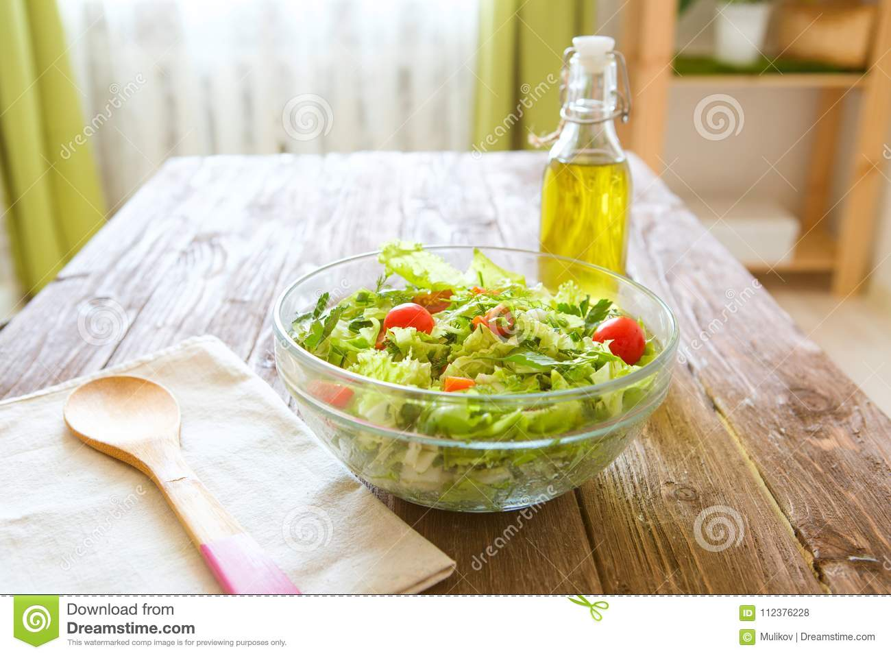 Full bowl of fresh green salad on a wooden table against on a rustic kitchen. Concept healthy lifestyle and simple food