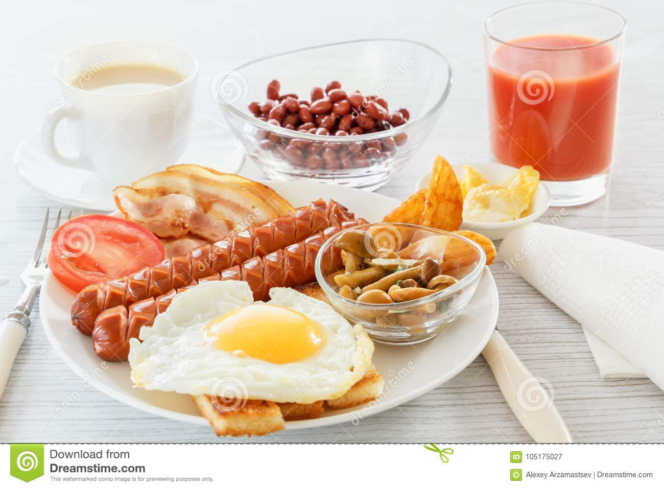 Full English breakfast with smoked sausages, fried egg, bacon, tomato, toast and beans. Tea with milk. A glass of fresh juice